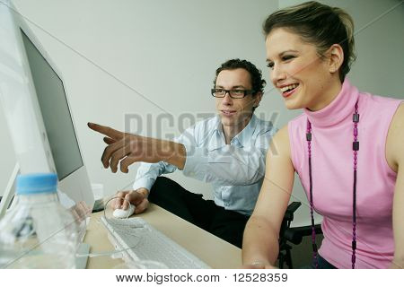 Smiling man showing the screen of a computer to a woman
