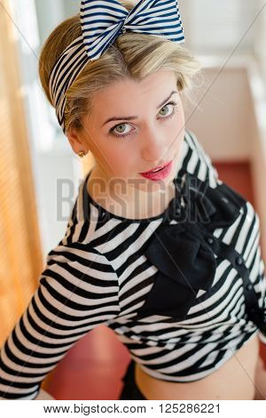 closeup image of pinup girl beautiful blond young woman in striped blouse having fun happy smiling looking  in camera on sun lighting windows background