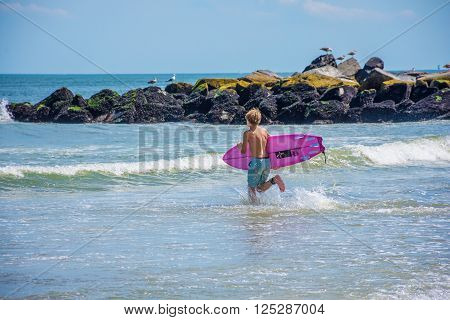 BELMAR NEW JERSEY-AUGUST 1 - A boy runs into the surf on a beautiful Summer day on August 1 2015 in Belmar New Jersey.