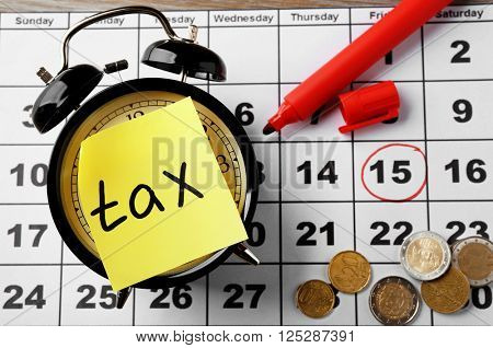 Tax time on alarm clock with coins, marker and calendar