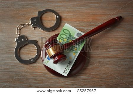 Law gavel with euro and handcuffs on wooden table background, closeup