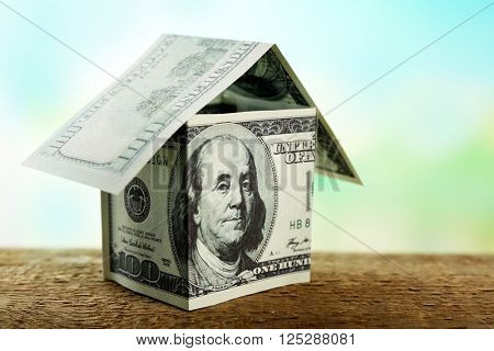 Money house on wooden surface, close up