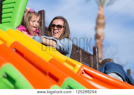 Mother in sunglasses with her daughter on bright chute