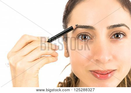Caucasian woman doing eyebrow painting with an eyebrow pencil. Isolated on white background.