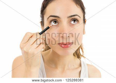 Caucasian woman applying eyeliner. Isolated on white background.