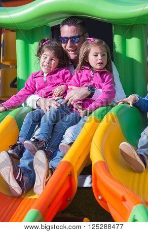 Happy family having fun on playground outdoor