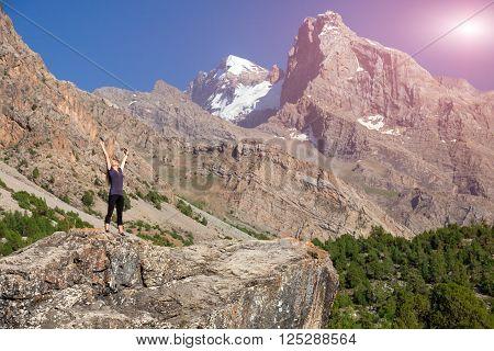 Female body on top of Stone Stretching body Towards Sun morning mountain landscape background Shining Sun