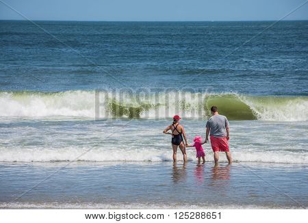 SPRING LAKE NEW JERSEY-AUGUST 1 - Parents hold their daughters hand in the surf on August 1 2015 in Spring Lake New Jersey.