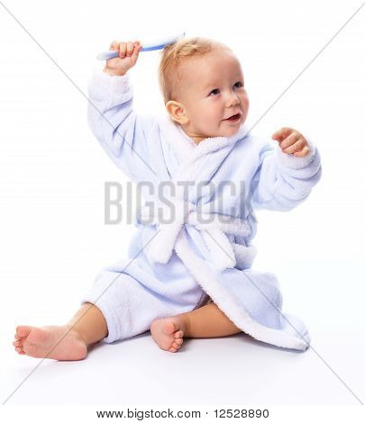 Cute Child In Bathrobe With Comb