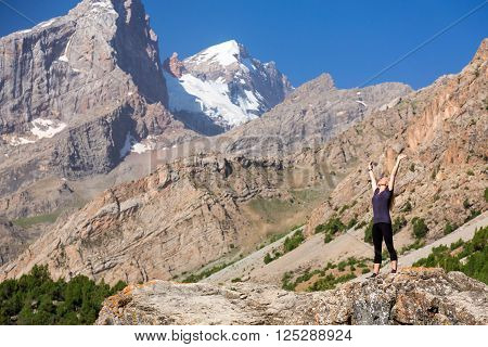 Attractive Young Woman Staying in Worshiping Posture  with Arms Raised Up  on Top of High Rock in Mountains