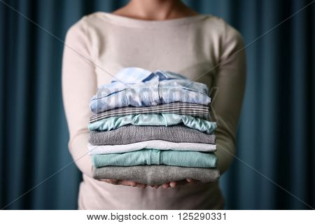 Woman holding washed and dried clothes on curtain background