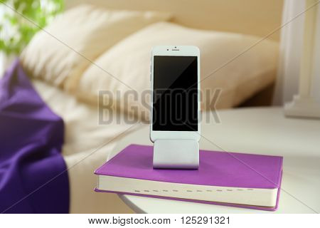 Smart phone with stand and book on a bedside table in a room