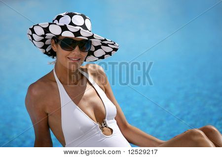 Portrait of a smiling woman in front of a swimming pool