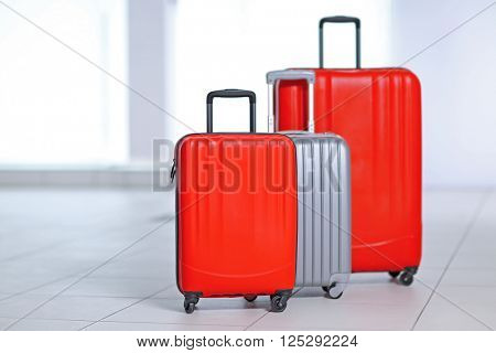 Three polycarbonate suitcases on the floor