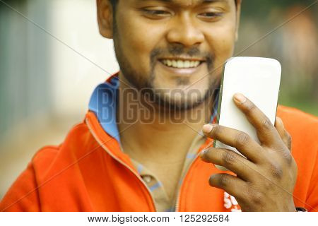 happy young indian man smiling as he looks on at his smartphone using internet with broadband wifi and 4g connected - concept of immigrants making use of technology to communicate with families