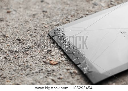 Broken tablet with cracked screen on the pavement