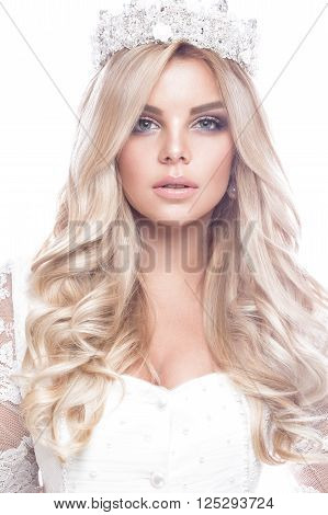 Beautiful blondie girl model in a lace wedding dress with curls and a crown on her head. The beauty of the face. Photos shot in the studio on a white background.