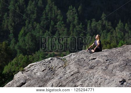 Attractive Female Athlete Sitting in Yoga Mediation Pose on Grey Rock Mountain Green Forest on Background