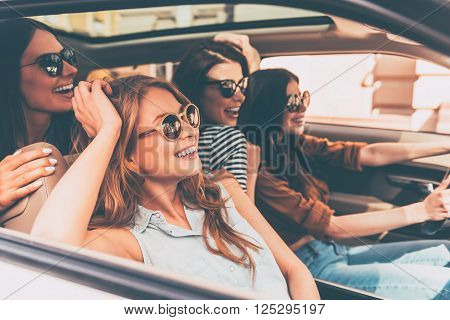 On the road together. Side view of four beautiful young cheerful women looking away with smile while sitting in car