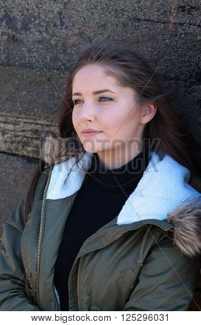 Beautiful young woman leaning against a wooden fence on a windy day