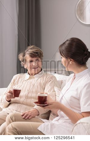 Young carer and friendly ward drinking tea together