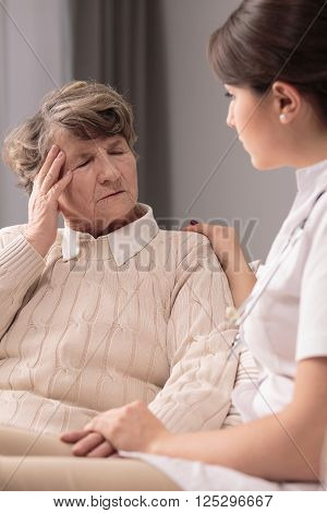 Elderly woman with terrible headache and supportive nurse