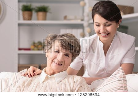 Smiling senior woman and her young pretty caregiver