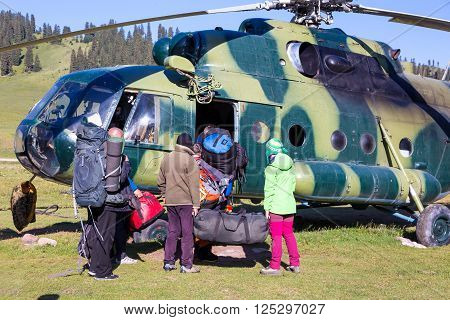 Helicopter Landing Ground and People Preparing for Boarding with Many Backpacks and Other Luggage on Green Meadow of Wild Kirghiz Steppe