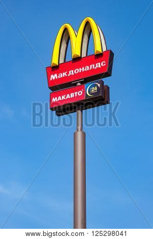 SAMARA RUSSIA - APRIL 10 2016: McDonald's logo on a pole against the blue sky. McDonald's is the world's largest chain of hamburger fast food restaurants
