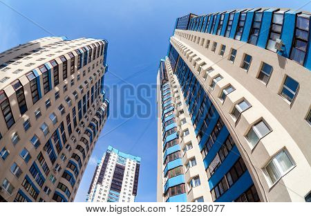 SAMARA RUSSIA - APRIL 10 2016: Fisheye view on the new tall apartment buildings against blue sky background
