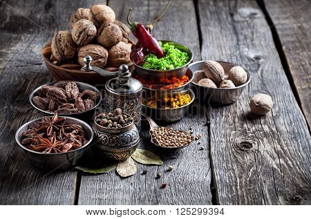 Spices And Nuts At Wooden Table