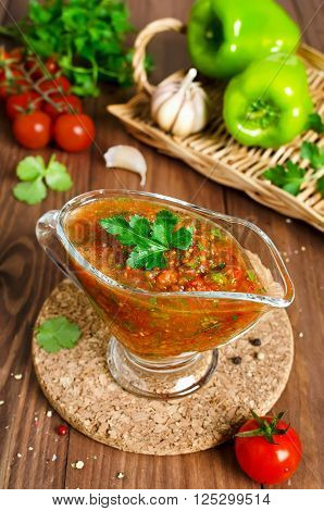 Fresh tomato sauce for meat on a wooden table. Sauce made from fresh tomatoes paprika garlic herbs and hot peppers