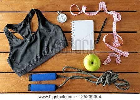 Athlete's set with female clothing, equipment, apple and notebook on wooden background