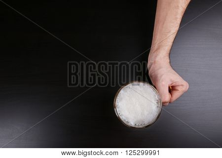 Male hand holding glass of beer on dark background