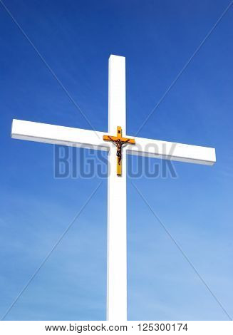 White catholic cross with crucifixion sign against blue sky