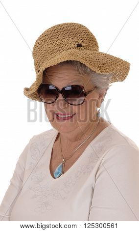 A lovely senior woman in her seventies wearing a straw hat and sunglasses smiling isolated for white background.