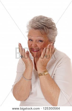 A gray haired senior citizen woman with her hands on her face smiling and is very happy isolated for white background.