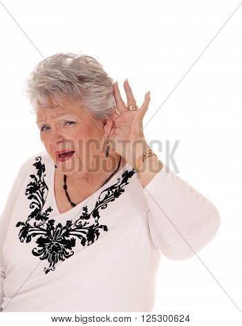 A lovely senior woman in her seventies has problem with hearing holding her hand behind her ear isolated for white background.