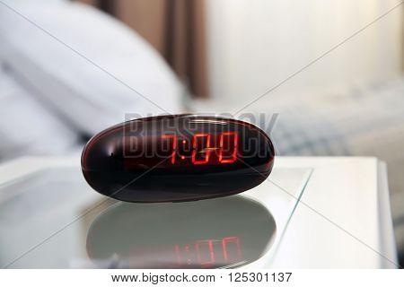 Digital clock on a bedside table in bedroom