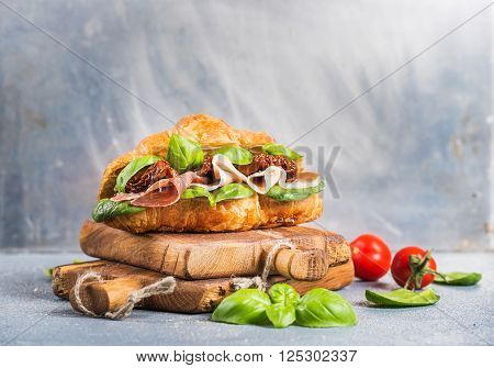 Croissant sandwich with smoked meat Prosciutto di Parma, sun dried tomatoes, fresh spinach and basil on stone textured grey background, selected focus