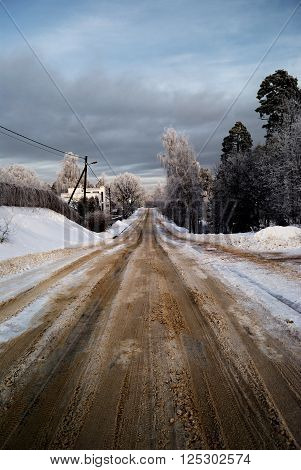 Snowcovered rural sand road in winter countryside.
