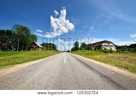 Open highway in a rural area with green fields and blue sky with beautiful clouds