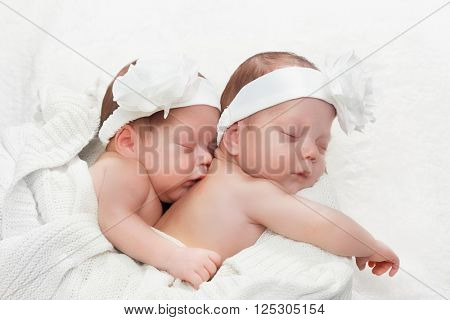 Newborn twins sisters sleeping and hugging each other, wearing white headband
