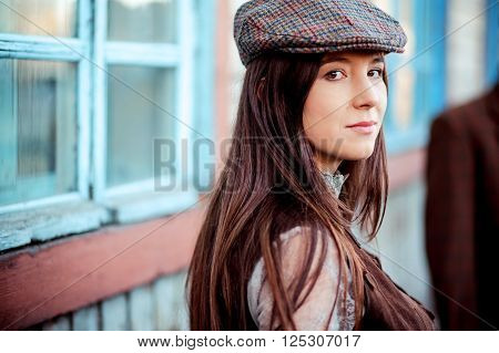 Young woman wearing tweed flat cap old fashioned portrait brown clothes, long hair.