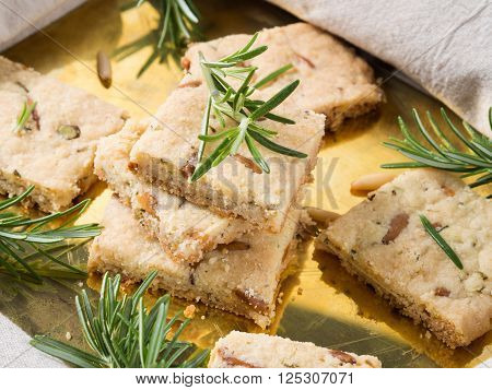 Butter cookies with rosemary, pignoli and pistachio nuts on golden tray, decorated with rosemary sprigs