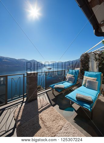 Terrace of house with comfortable sun beds, lake view