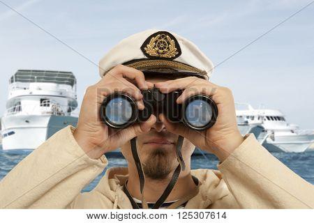 Captain looks through a binoculars. Marine concept