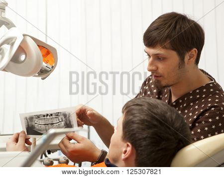 Dentist giving medical consulting to men. Dental photo series