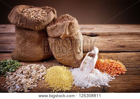 Krupa scoop, wooden spoon, an assortment of cereals, a table of old wood, the grain harvest, organic food, a bag of barley, texture of old wood, kitchen utensils, health food, scattering grains.