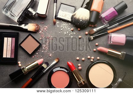 Frame of decorative cosmetics and accessories for makeup on grey background